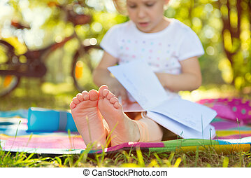Cute child sitting on grass with book. Foots in focus