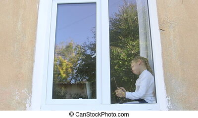 Cute child sitting on the window immersed in game with digital tablet