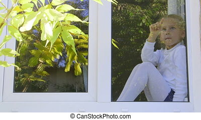 Cute child sitting on the window in autumn