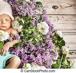 Cute child sleeping on the flowers