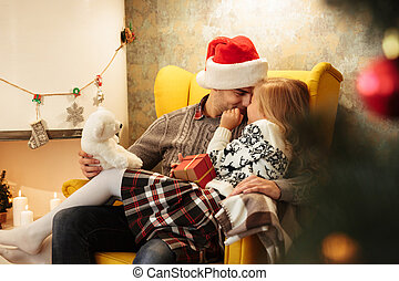 Cute child touching her father with nose while sitting on his knees in living room with Christmas decor