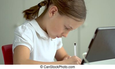 Cute child use laptop for education, online study. Girl has homework at home schooling. Communication with the teacher remotely.