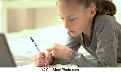 Cute child use laptop for education, online study. Girl has homework at home schooling.