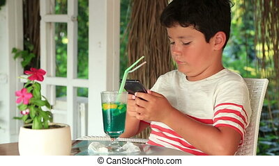 Cute child using smartphone at the summer cafe - Young boy...
