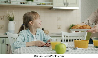 Cute child is using smartphone touching screen when mother is bringing plate of fresh croissants in kitchen in apartment. Family life and devices concept.