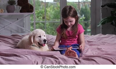 Cute child watching video with puppy on bed - Serious...