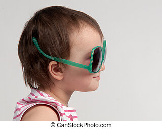 Cute child wearing glasses in a wrong way