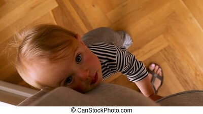 Cute child with big eyes standing on legs holding onto...