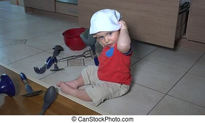 Cute child with chef hat doing mess in kitchen. Toddler boy...