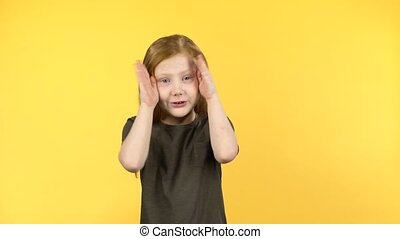 Cute child with red hair have fun covers her face with hands