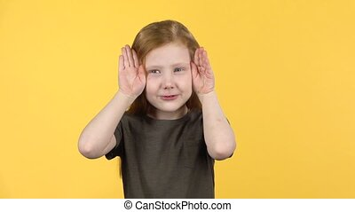 Cute child with red hair have fun covers her face with hands. Slow motion