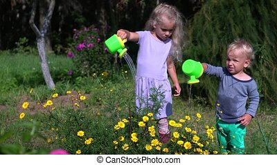 Cute children brother and sister water flowers with small watering can in garden