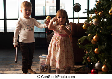 Cute children decorating Christmas tree with toys