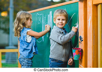 Cute children drawing with chalk on blackboard outdoor