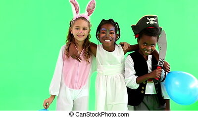 Cute children dressed up in costumes on green background