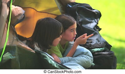 Cute children in a tent looking at something in a park