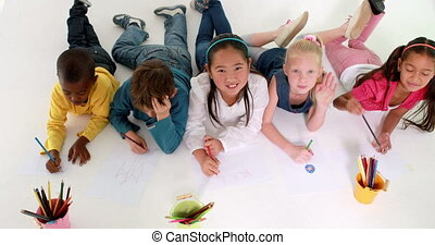 Cute children lying on floor drawing on paper and waving at...