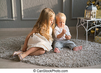 Cute children playing together near Christmas tree indoors.