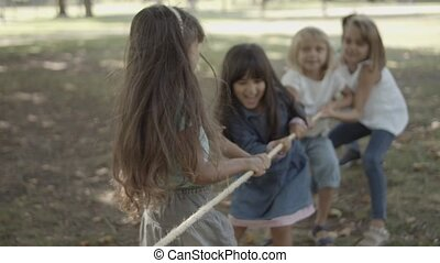 Cute children playing tug-of-war and testing their strength