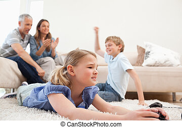 Cute children playing video games with their parents on the background in the living room
