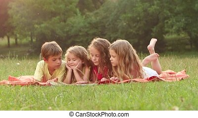 Cute children reading a book in the garden together summer a...