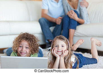 Cute children using a laptop while their parents are watching