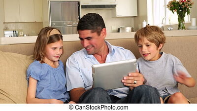 Cute children using tablet with father on couch at home in...