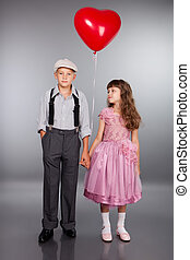 Cute children walk with a red balloon