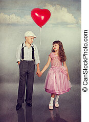 Cute children walking with a red balloon