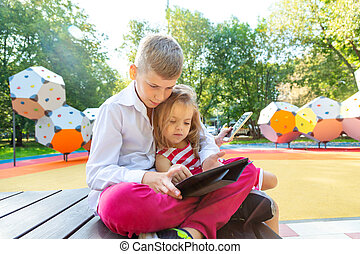 cute child's with phones setting and using a tablet - brother embrace his sister