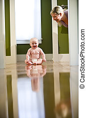 Cute chubby baby wearing diaper sitting on floor laughing at mother