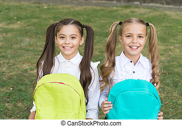 Cute classmates girls with backpacks, knowledge day concept.