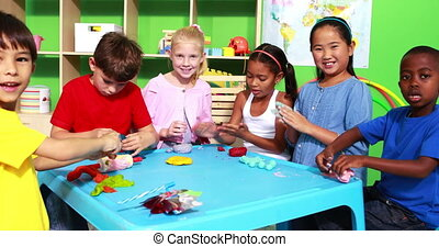 Cute classmates playing with clay and waving at camera in ...