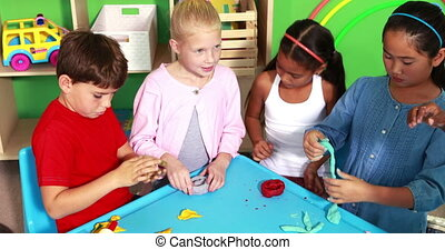 Cute classmates playing with clay in playschool