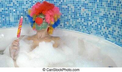 Cute clown man in a bathtub with plentiful foam eats a ...