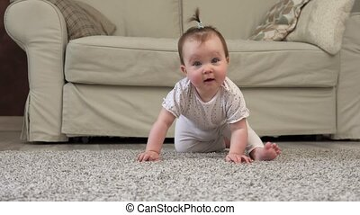 Cute clumsy baby smiling and looking at camera on floor at...