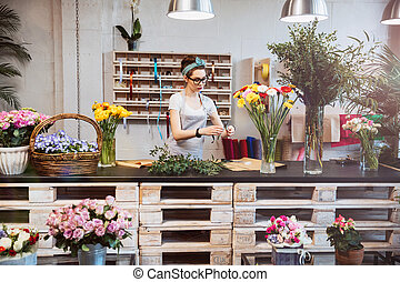 Cute concentrated female florist working in flower shop -...