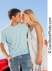 Cute couple against their red cabriolet kissing