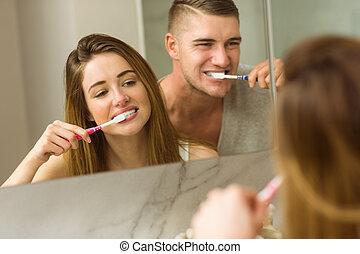 Cute couple brushing their teeth