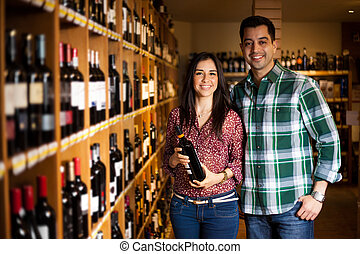 Cute couple buying a bottle of wine