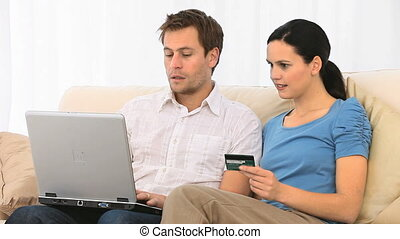 Cute couple buying on the net in their living room