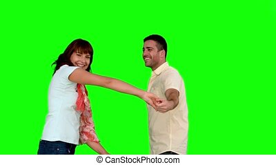 Cute couple dancing on green screen in slow motion