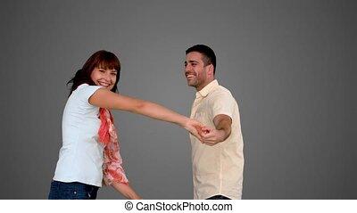 Cute couple dancing on grey backgro