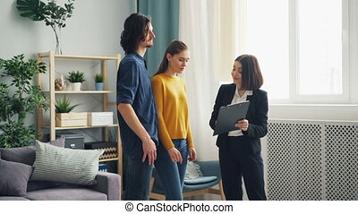 Cute couple discussing mortgage contract with realtor talking indoors at home