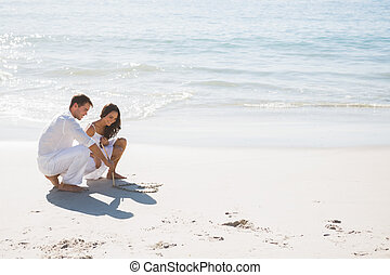 Cute couple drawing a heart in the sand