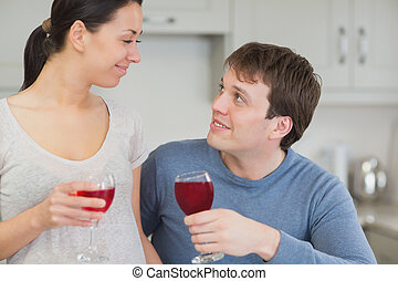 Cute couple drinking red wine and looking at each other