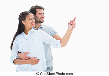Cute couple embracing and pointing