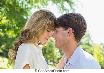 Cute couple facing each other in the park