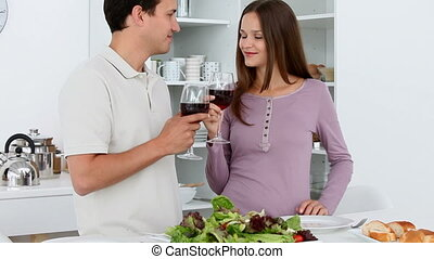 Cute couple giving a toast while having lunch