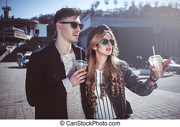 Cute couple having fun walking at the street and drink cocktails